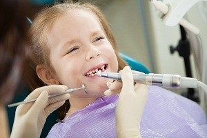 Child feels toothache during polishing procedure in dentist chair