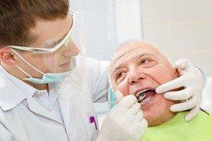 Closeup portrait of young dentist  treating senior elderly man